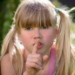 Girl with her finger on her lips encouraging silence.