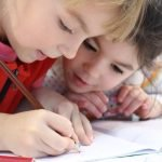 Two girls writing their ideas. Keeping the students involved in all stages of the process can help them remain enthused.