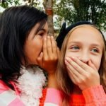 Two girls whispering. Speed whispers is a drama game in which students must whisper a phrase to eachother in teams. It improves teamwork, focus, pronunciation and is an effective TEFL activity.