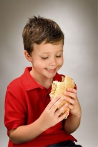A child smiling while holding a sandwich. Implied that it is a poop sandwich.