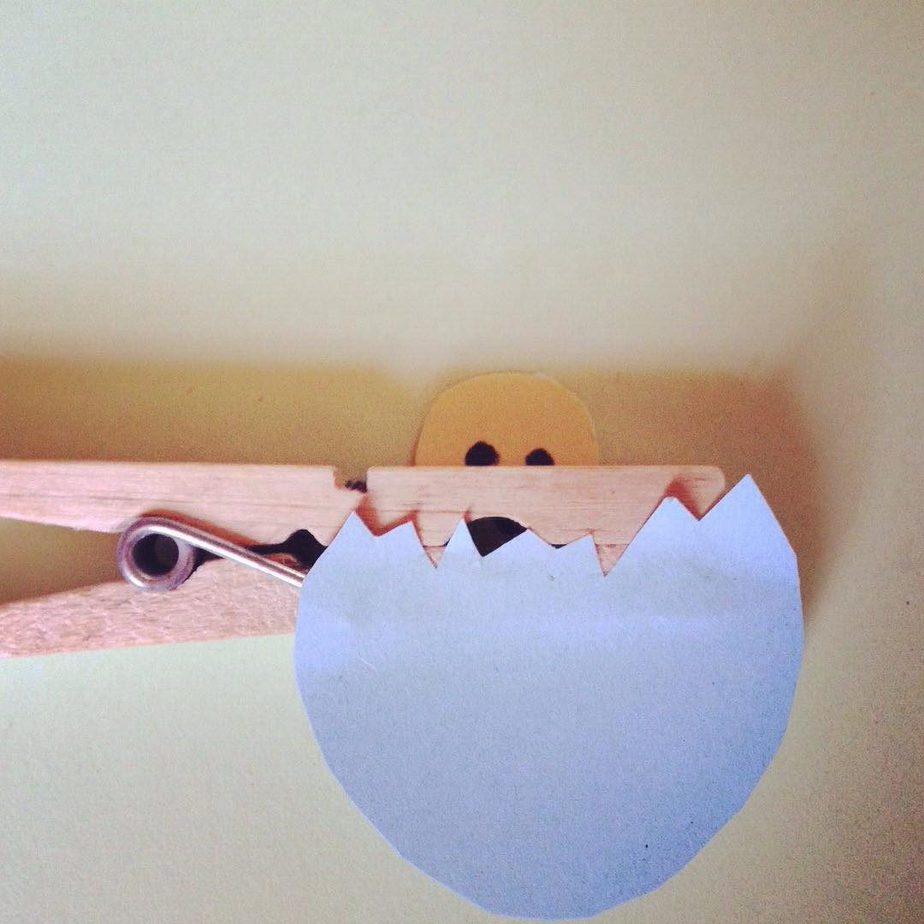 Stick the bottom half of your egg to the bottom half of the peg, facing outwards and on the opposite side to the chick.