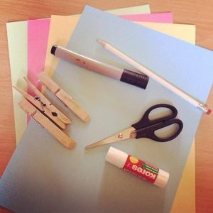 You will need scissors, glue, clothes pegs, coloured card, a pencil and coloring pens.